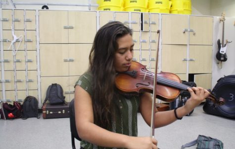Junior, Julie Cons playing the violin during Orchestra.