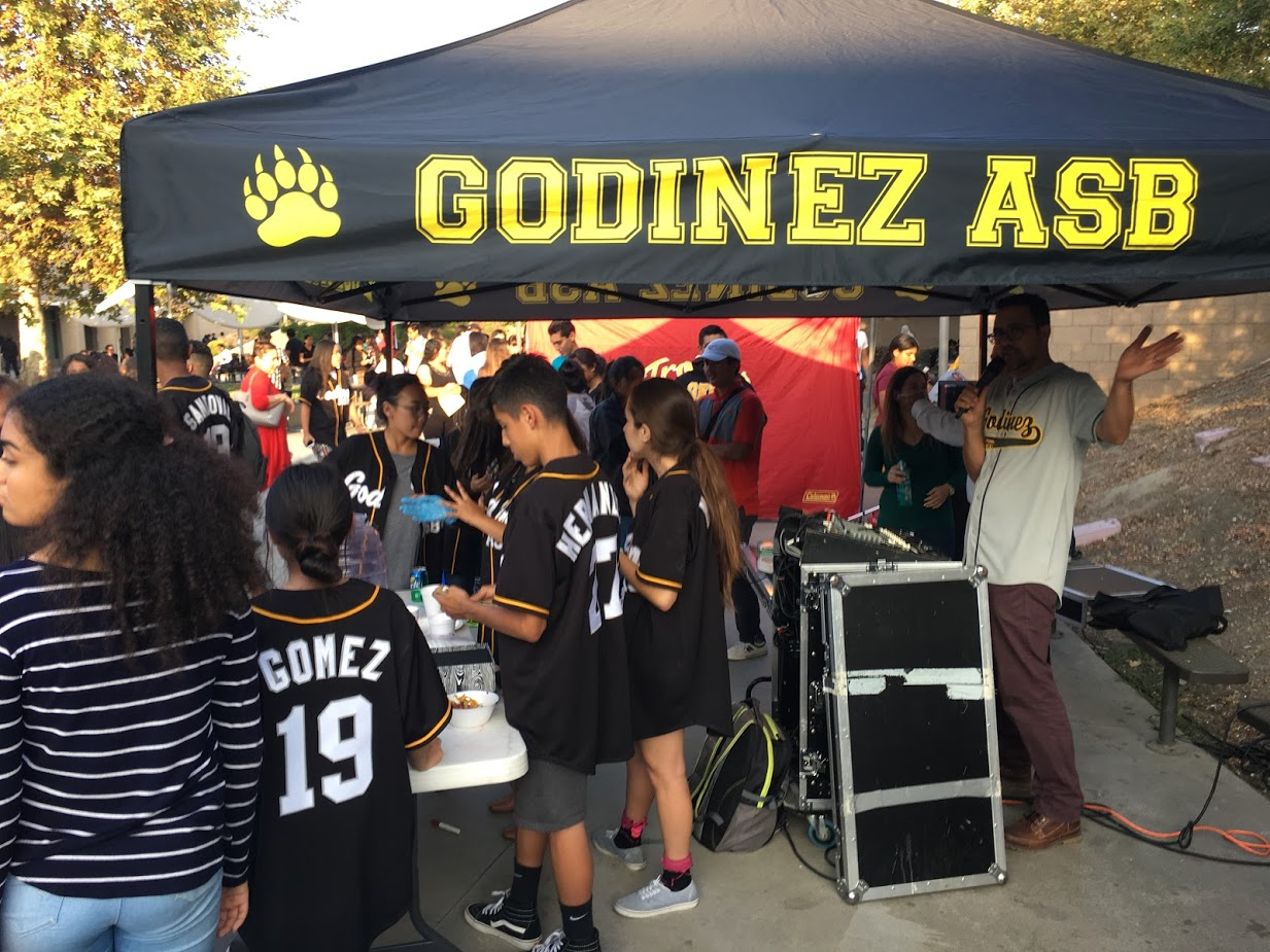 ASB selling aguas frescas to people while Mr. Tena announces upcoming performances.