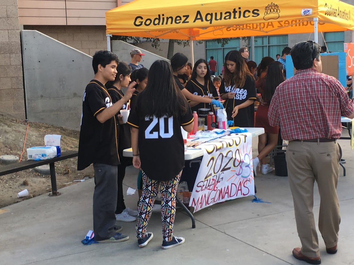 The Godinez ASB class of 2020 selling mangonadas as customers gather around and wait patiently for their turn.