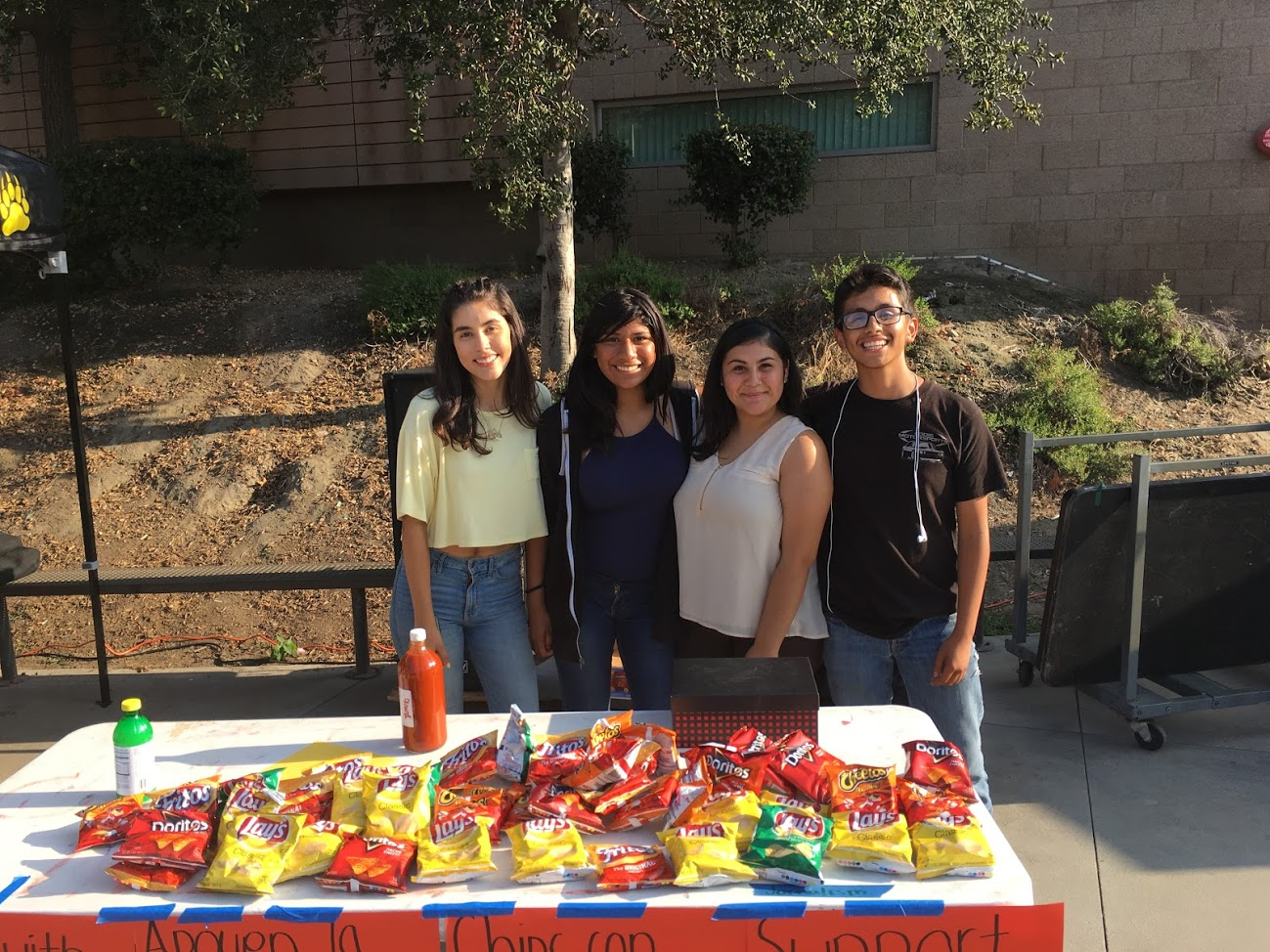 Journalism class of 2017-18 selling a variety of chips while they pose for a picture after a long day of sales.