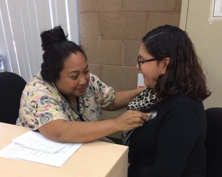 Teacher Marlyn Desper listens to junior Sara Gonzalez heartbeat.