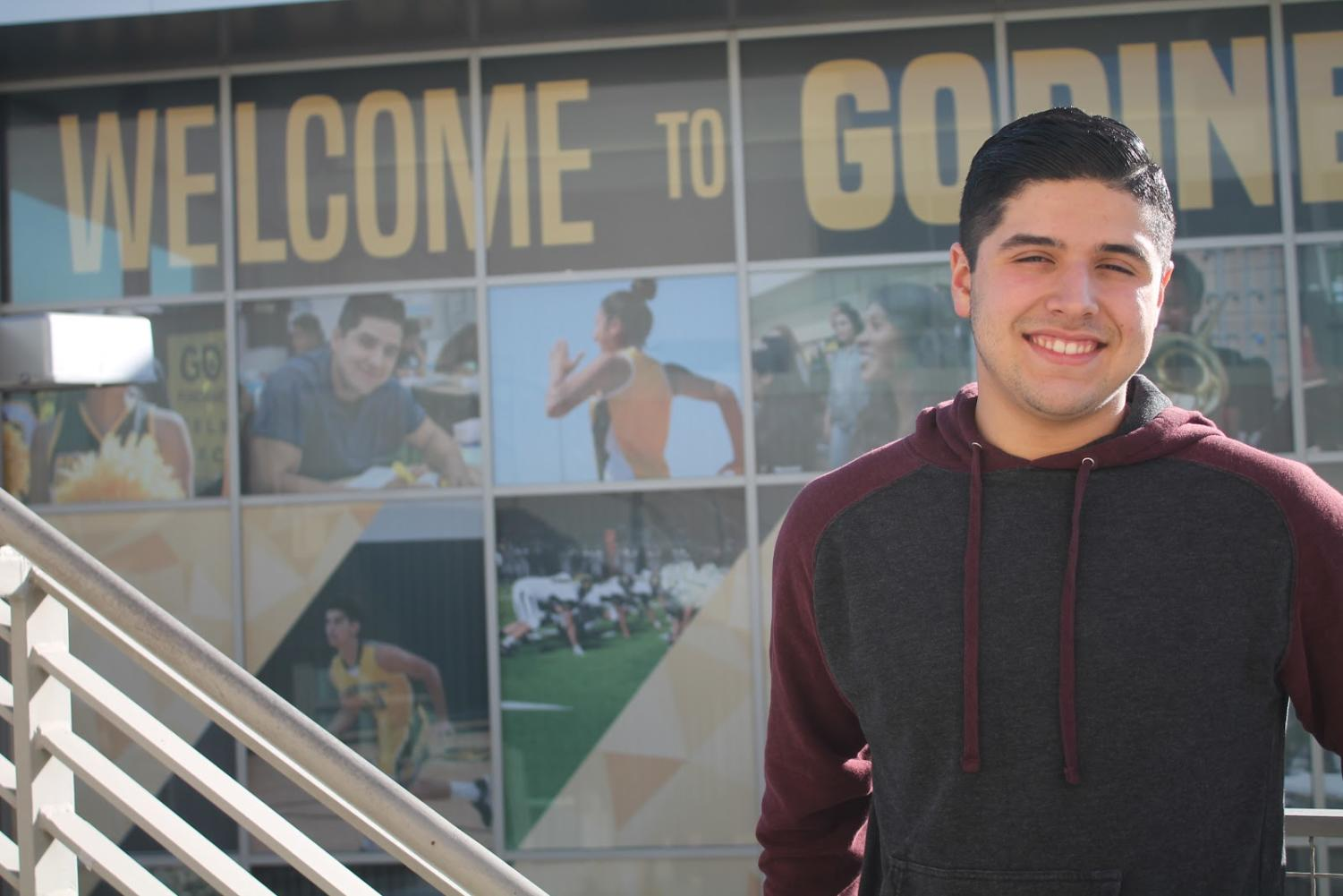Senior Julio Ortega stands in front of the new window coverings that features himself.