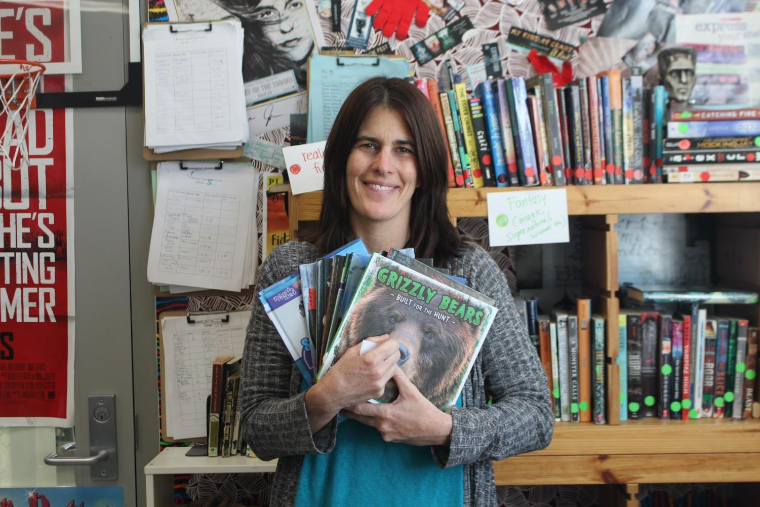 Teacher Lori Polydoros in her classroom, holds just some of the books she has written.