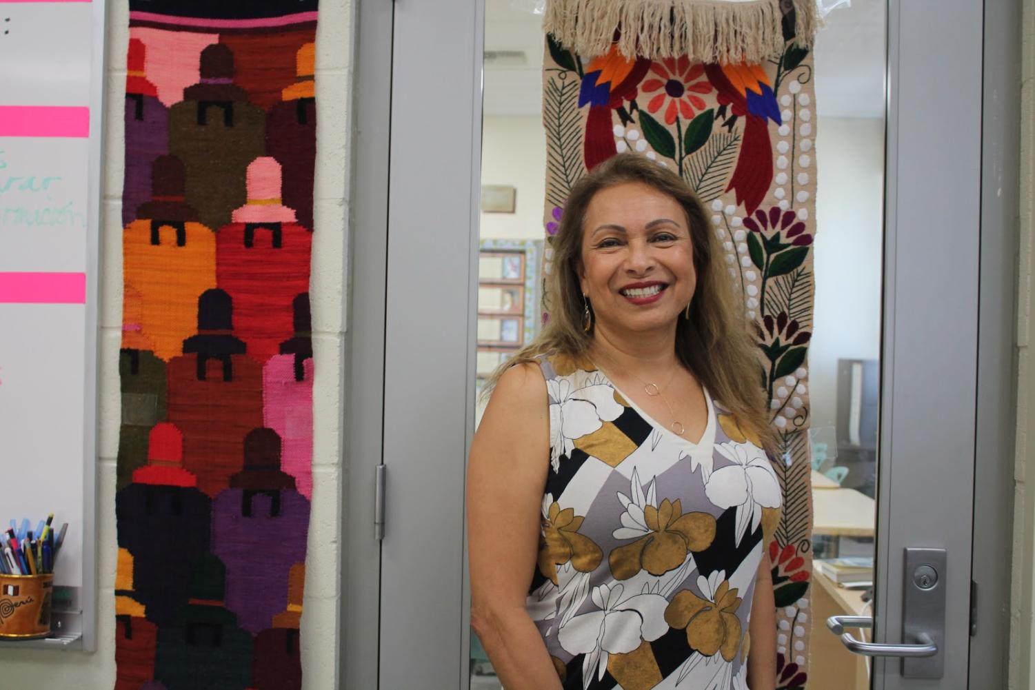 Spanish teacher Elvia Morales standing besides her Mexican mosaic tapestries.