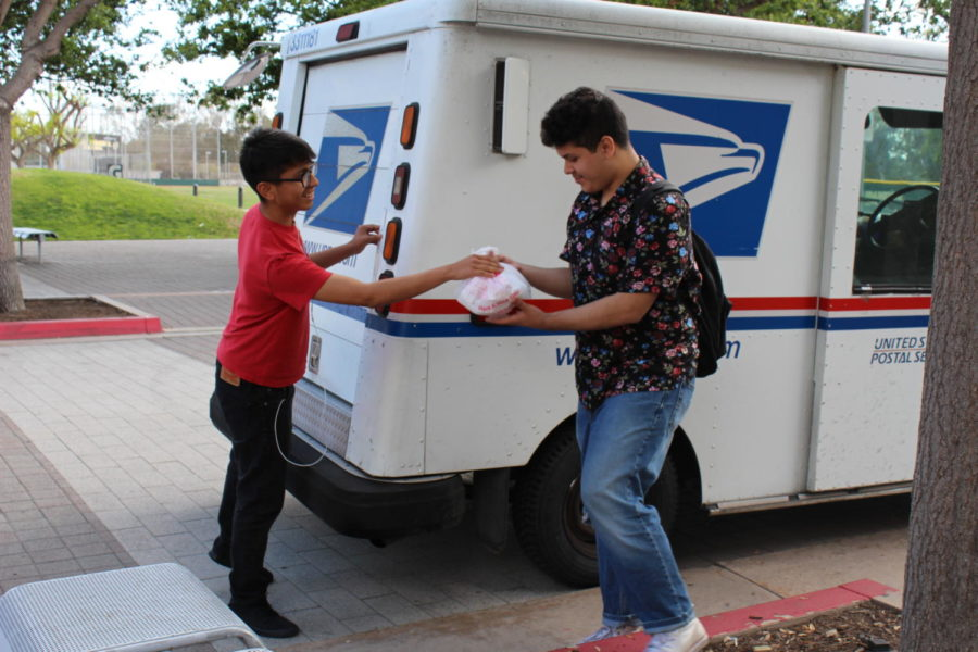 From left: Bryan Rivera, a senior, receives contraband from Steve Pineda in front of the school.