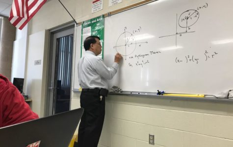 Teacher Todd Oishi busy at the board working out a math problem in his soon-to-be vacant classroom.