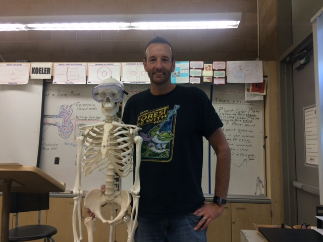 "Human anatomy and Biology teacher: James Koeler stands next to his skeleton.     Nov. 09, 2018 photo by Ana Orozco Koeler and his family like to feast during Thanksgiving break.  "" I like to do a stuffing that  my dad taught me that he learned from his mother."" They like to eat turkey, apples and pumpkin pie. Koeler loves to eat a Long Island fish crap dip with cheese crackers."