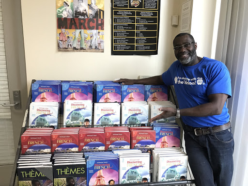 French teacher Eric Pierre standing besides his bookshelf of French textbooks.
