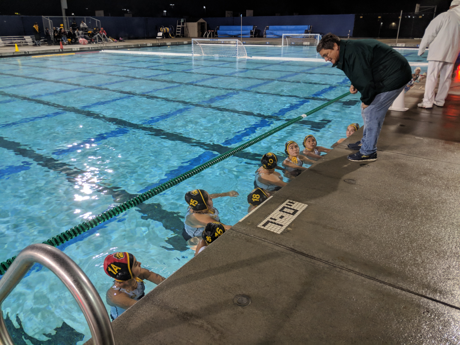 Coach John Wright gives his game plan during a game against Western High School. Varsity girls lost to Western 9-2. Photo taken at Valley High School's pool on Jan. 30, 2019.