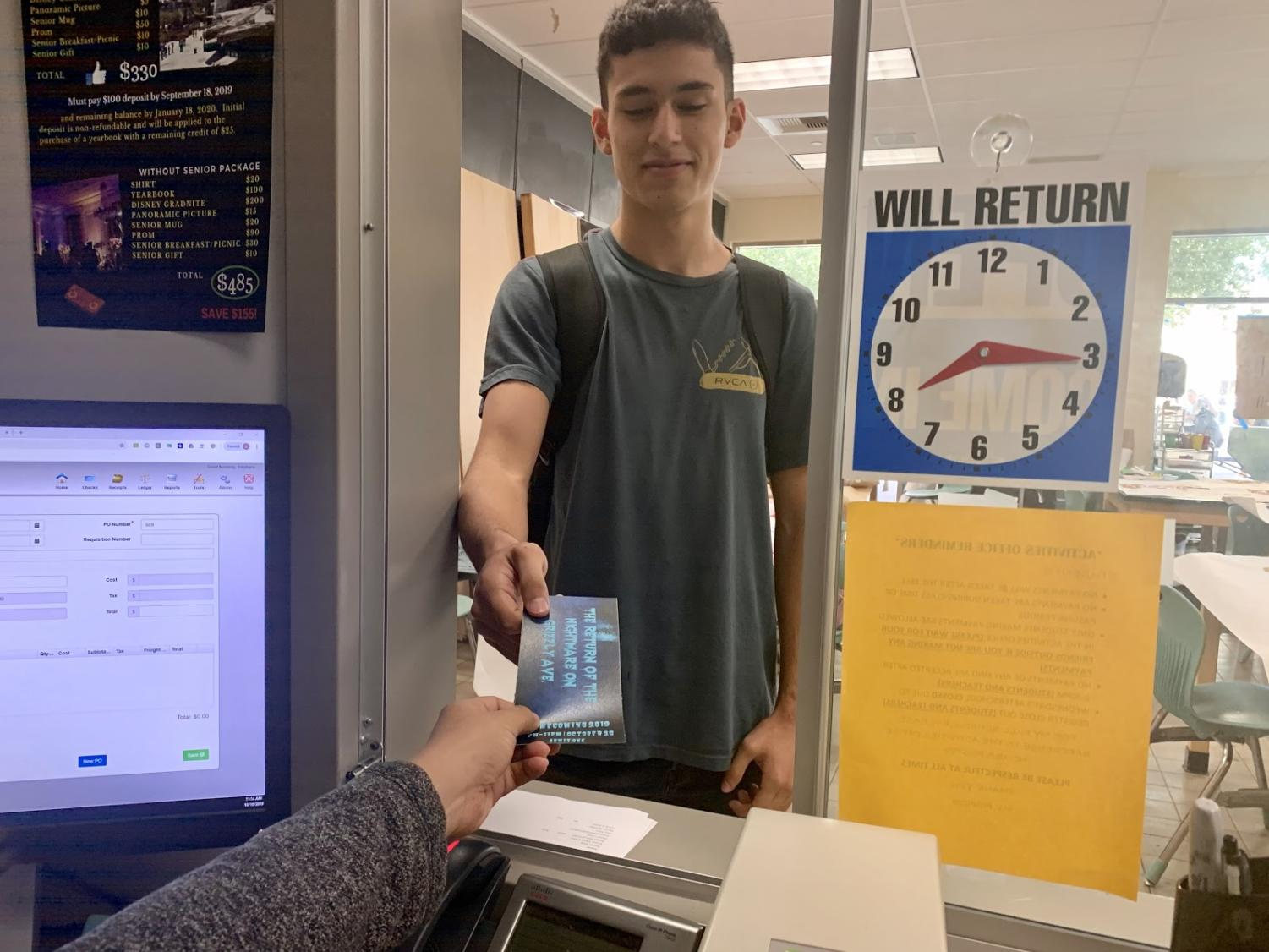 During 1st lunch, Senior Adrian Alvarez purchases a homecoming ticket from the Activities Office. Photo taken Oct. 10, 2019, inside the ASB room.