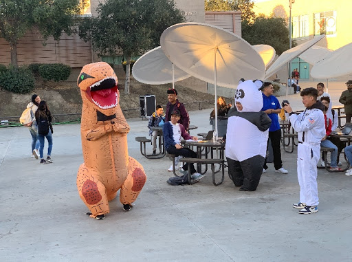 From left to right: Melvin Leon (dinosaur), Moises Cerda (panda), and photographer Roman Arcos (NASA astronaut) takes a few photos of the Halloween