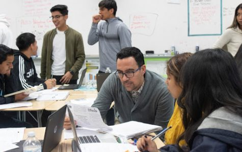 Daniel Tena helps students with homework during his first period AVID class.
