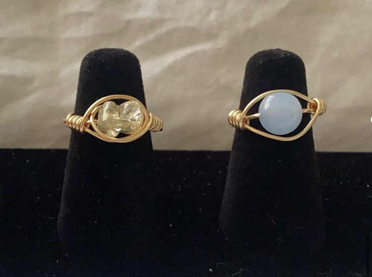 From left, Roa's personal favorite, gold wired Citrine crystal ring and gold wired sky blue bead ring are displayed. Citrine crystals bring motivation and positive energy, cleanses and revitalizes the mind, and much more.