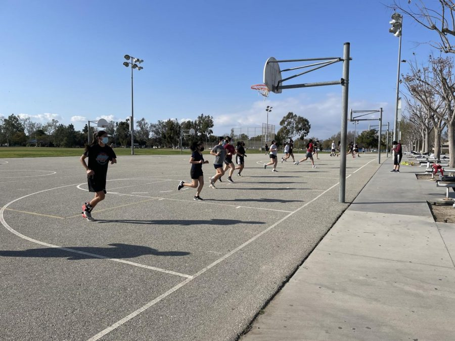 Girls basketball team practices some drills on the black top at Godinez's basketball courts. Photo taken March 8, 2021 at 3:21 p.m.   As of now, only varsity girls basketball are playing. Their first game is scheduled for April 9th, 2021 against Santiago at 7 p.m. However, there are many more to come with an approximate of 15 games.