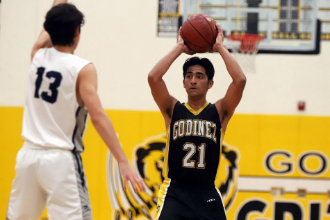 Varsity basketball player Christopher Figueroa making a pass in a game