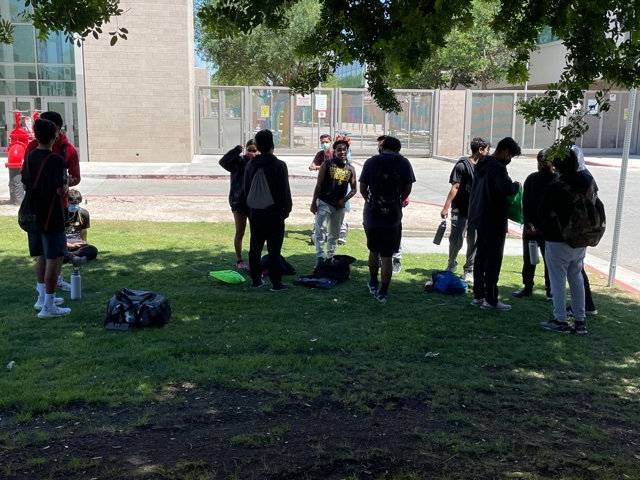 The boys track and field team patiently wait for the bus behind Godinez to take them to Segerstrom. Photo taken April 28, 2021 at 1:53 p.m.