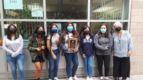 Science teacher, Dr. Apostol and the rest of environmental club stand outside room 2-112 holding the leadership award.